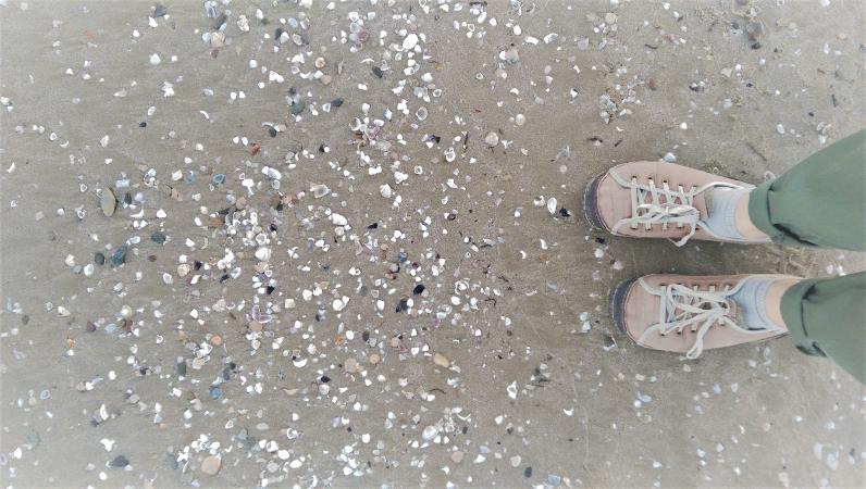 odpowiedzialność to ciągłe wybory - zdjęcie przedstawia stopy w trampkach nad brzegiem morza - widoczne są małe muszelki na piasku