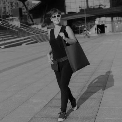 Duża czarna torba na ramię prezentuje Justyna - zdjęcie czarnobiałe, modelka idzie na tle dworca fabrycznego w Łodzi, torba na ramię jest czarna (również w rzeczywistości) z jednym uchwytem i sięga Justynie do uda.