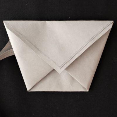 szara kopertówka w kształcie koperty - trapezu wykonana z washpapy - specjalnego materiały jak papier, który można prać i prasować