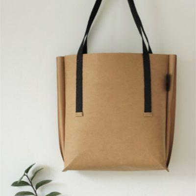 duża jasno brązowa torba z papieru do szycia i prania, o kroju szoperki, z szerokim bokiem. Ucha torby są wykonane z czarnej taśmy konopnej. Na prawdę duża!
