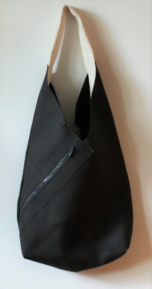 """torba lniana z grubego czarnego brezentu lnianego o wydłużonym kształcie. Otwarta, na szerokim pasku na ramię, z charakterystyczną kieszenią zewnętrzną """"na ukos"""" zapinaną na zamek."""