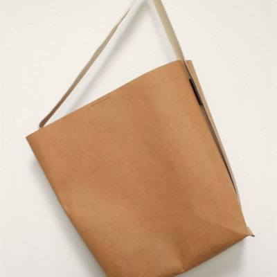 bardzo prosta torba z papieru z pojedynczym uchwytem na ramię. W kolorze łupinki orzecha włoskiego.