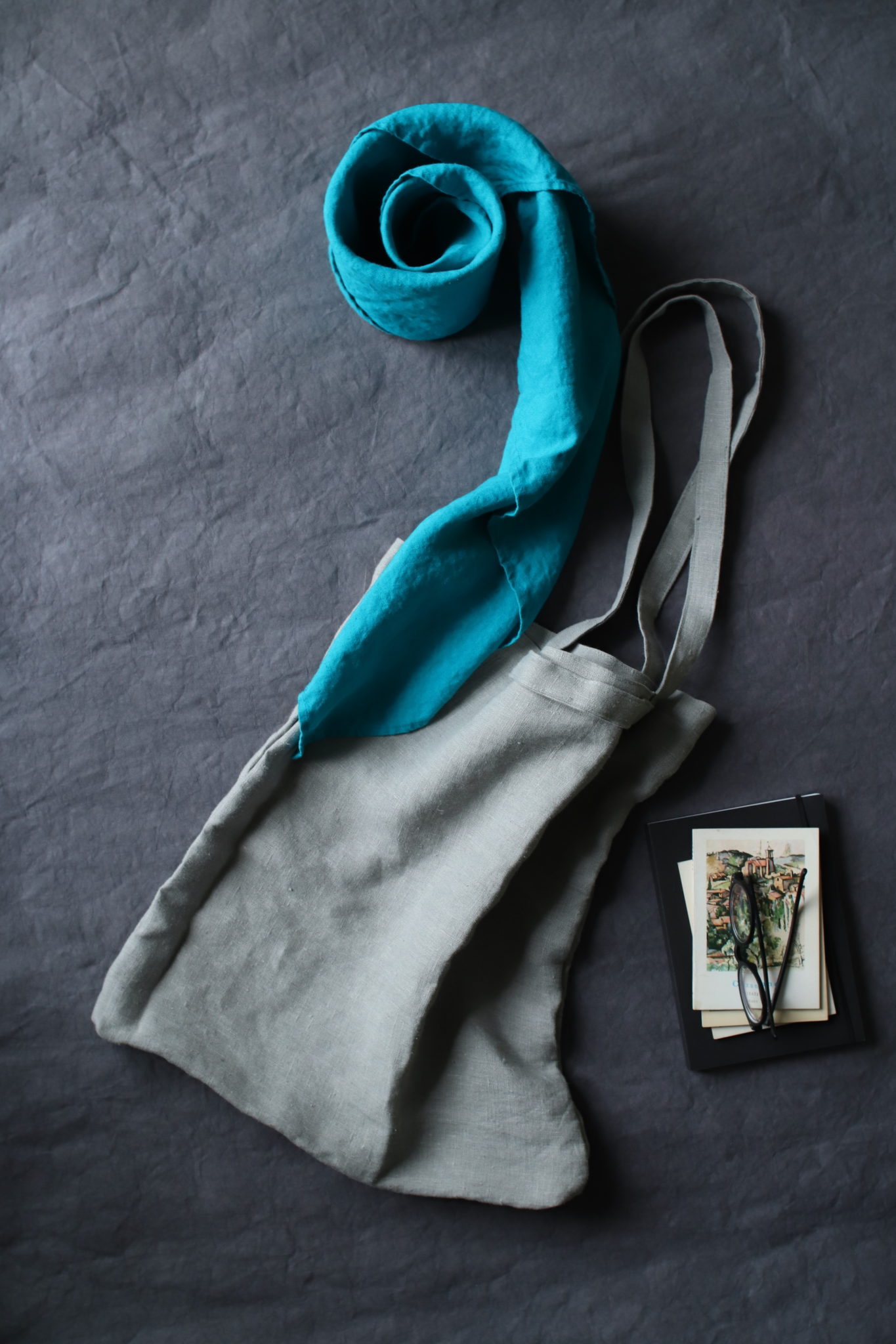 torba lniana naturalna w kolorze jasno-szarym lekko w lekko zielonkawym odcieniu w kompozycji na grafitowym tle z turkusową chustą lnianą