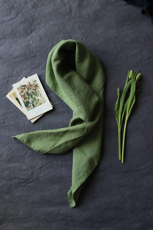 zielona chusta lniana w towarzystwie zielonych tulipanów o tym samym odcieniu